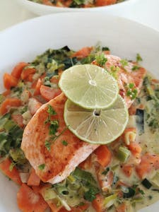 Salmon served on top of creamy vegetables
